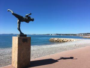 Statue en bronze représentant une muse en équilibre avec la mer et les plages de galet en fond